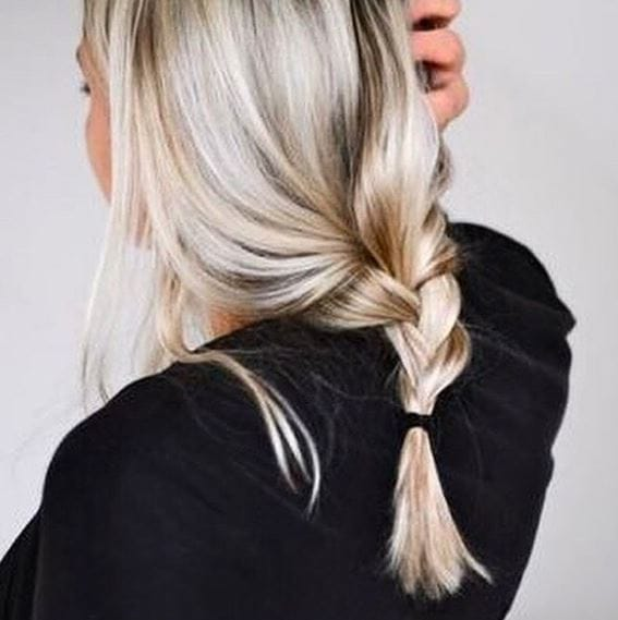 back shot of a woman with icy blonde hair and highlights in a loose plait