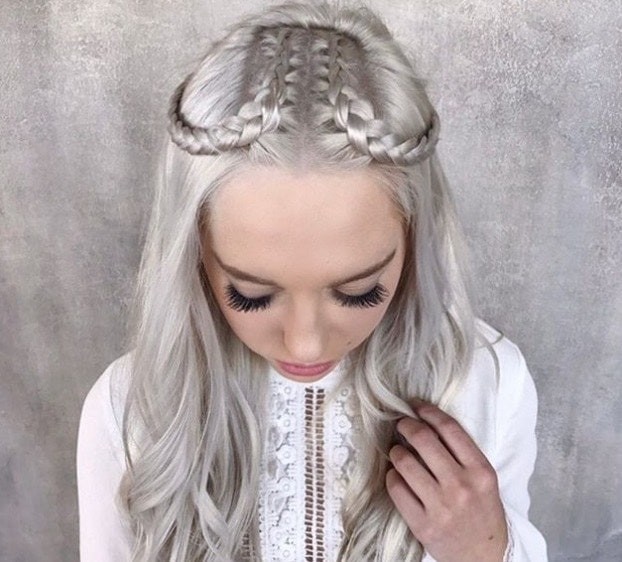 down prom hair: close up shot of woman silver grey hair styled into a half-up crown plait, wearing white dress and posing in a studio