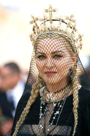 Madonna hair: Madonna at the 2018 Met Gala with her blonde hair in two pigtail braids with a black veil and gold crown.