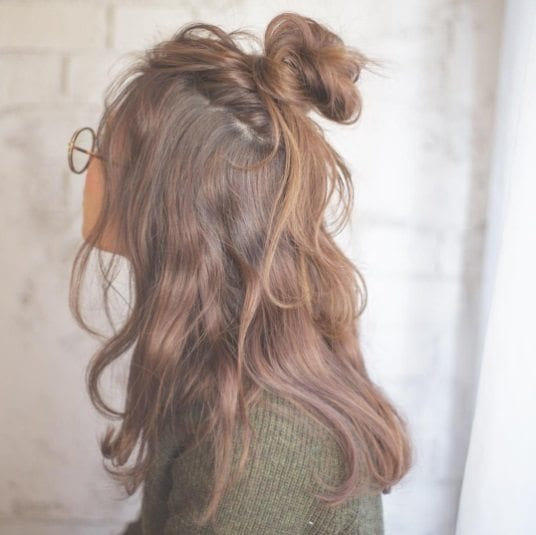 woman with long brunette hair in a half up half down messy bun