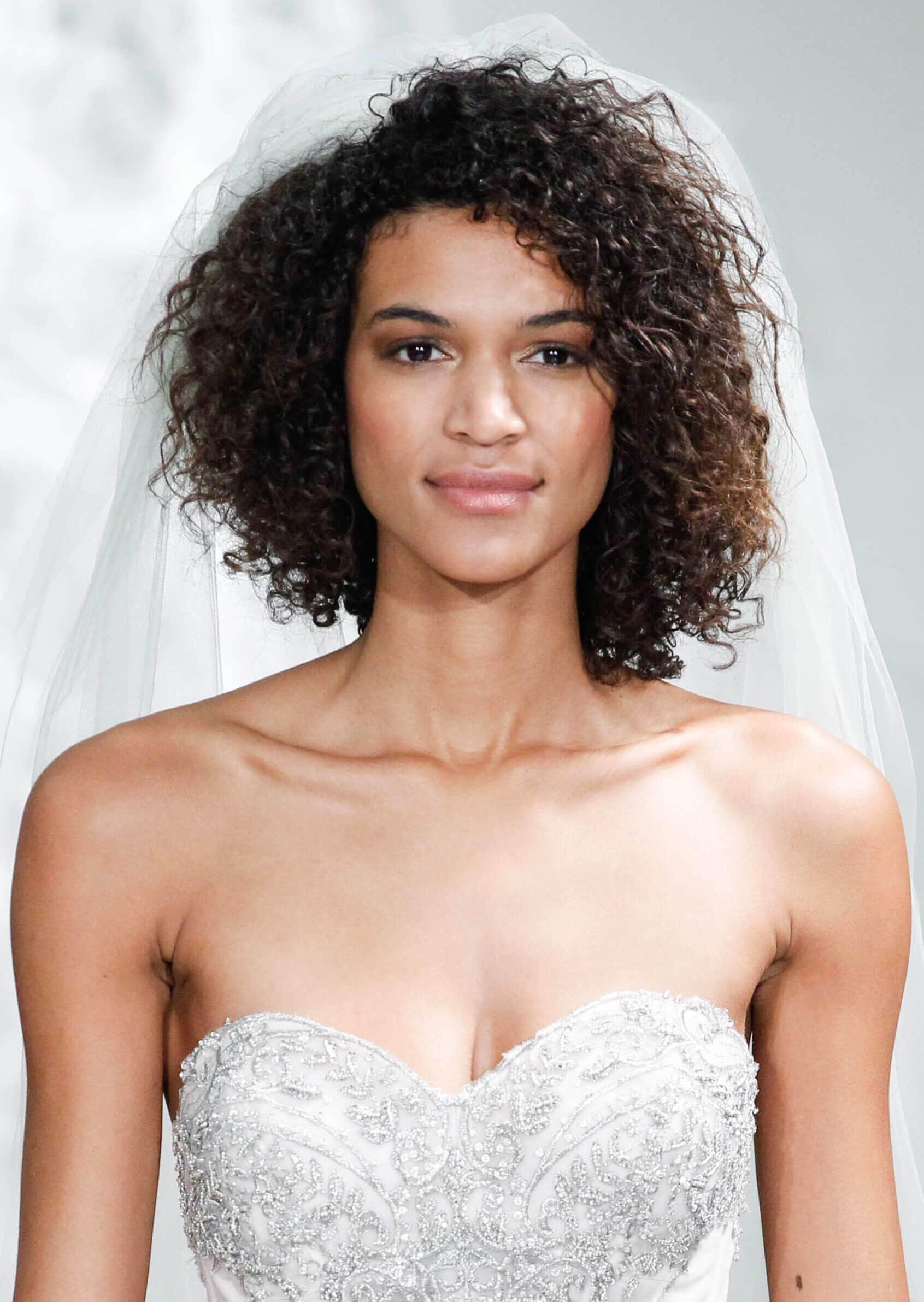 model on the bridal runway with curly twist out hairstyle with viel