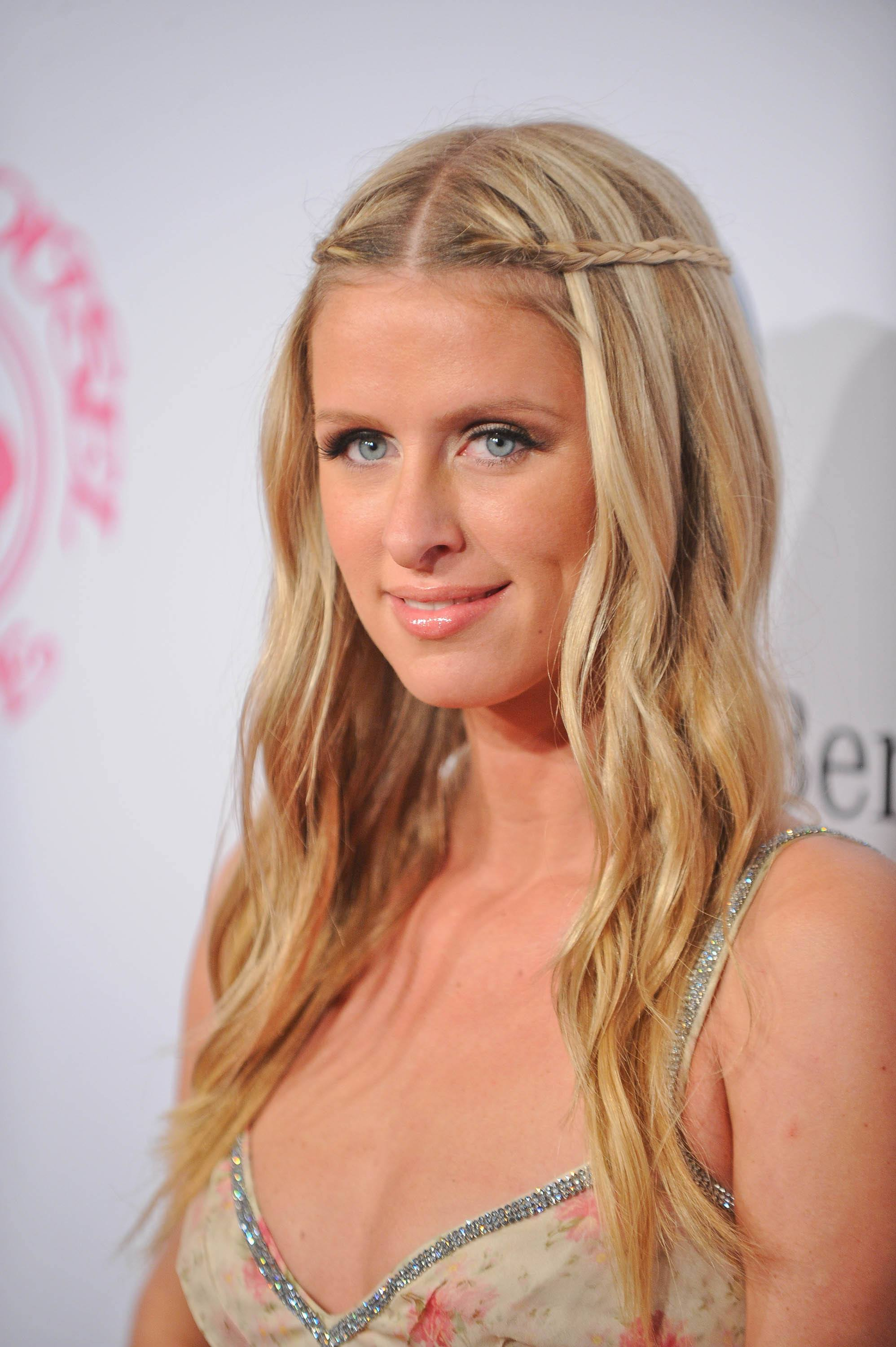 shot of nicky hilton on the red carpet with a long and simple half up braided hairstyle, smiling and wearing a summer dress