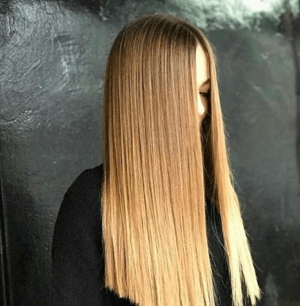 model with very long hair with brown to blonde ombre finish in poker straight style