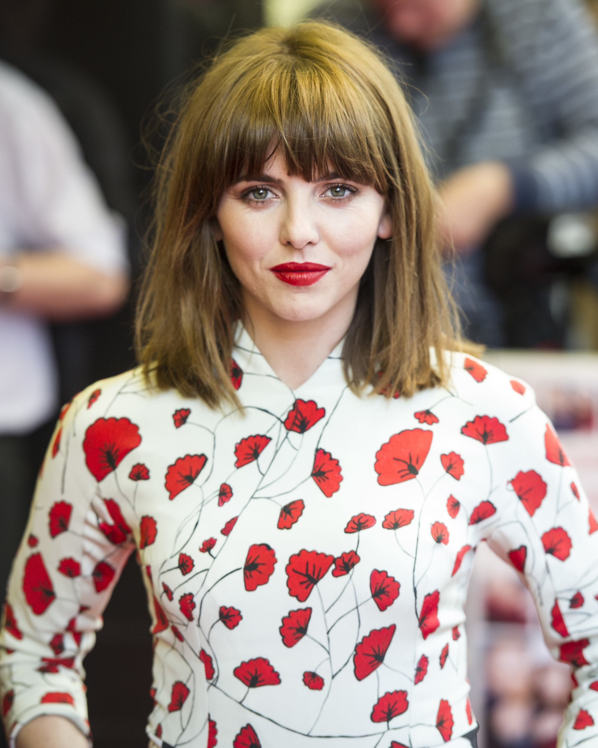 1970s short hairstyles: ophelia lovibond with 70s-inspired long bangs and short medium bob hairstyle