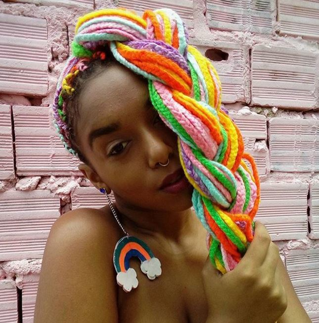 front view of girl with rainbow coloured box braids in high ponytail braid covering her face