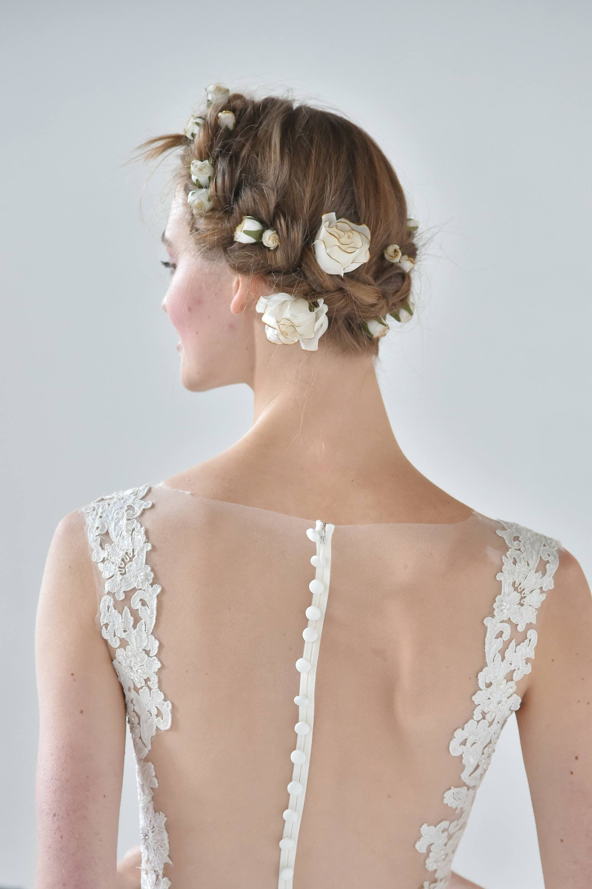 backshot of model with milkmaid braided hairstyle updo with flowers
