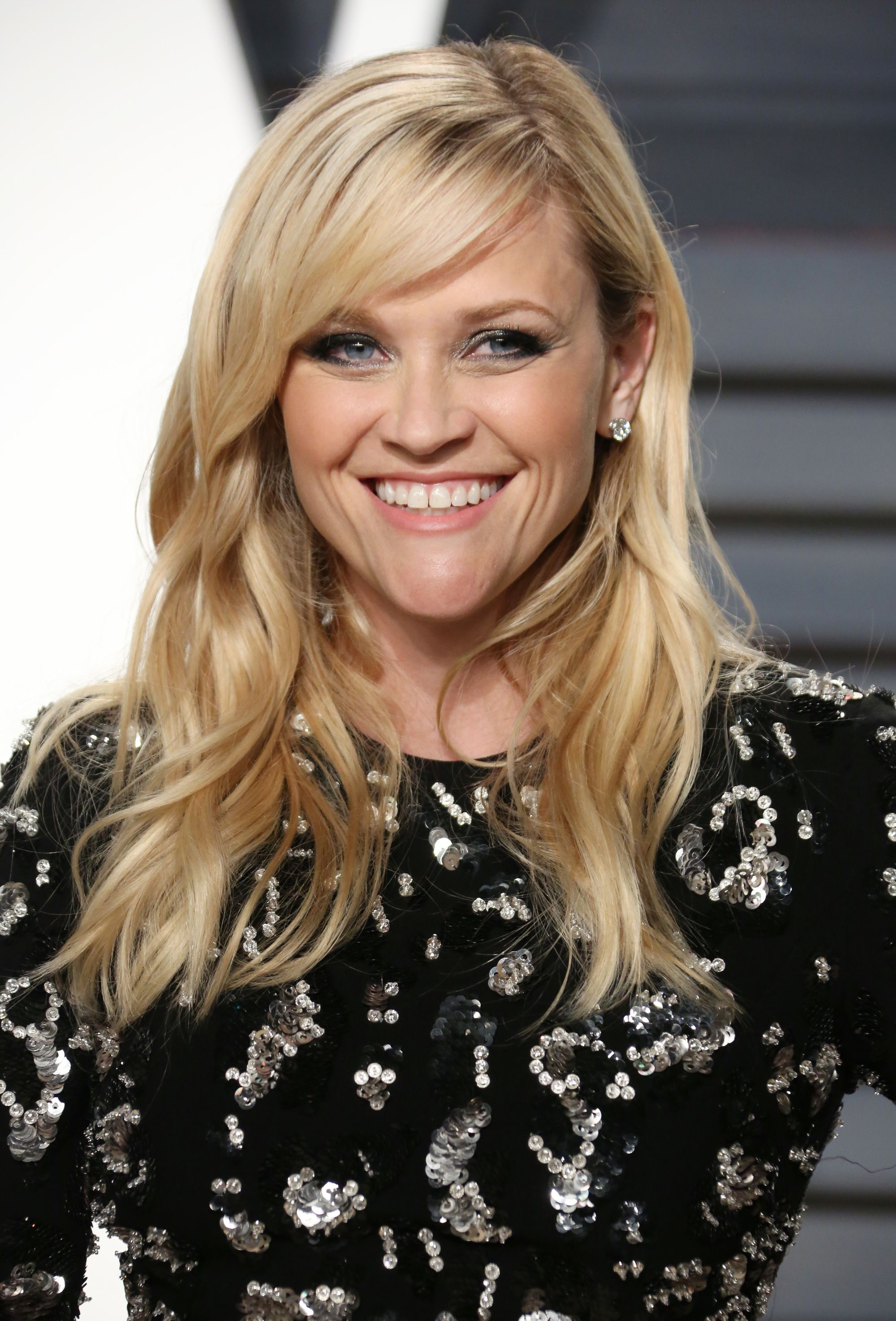 actress reese witherspoon with blonde side bangs and curly hair