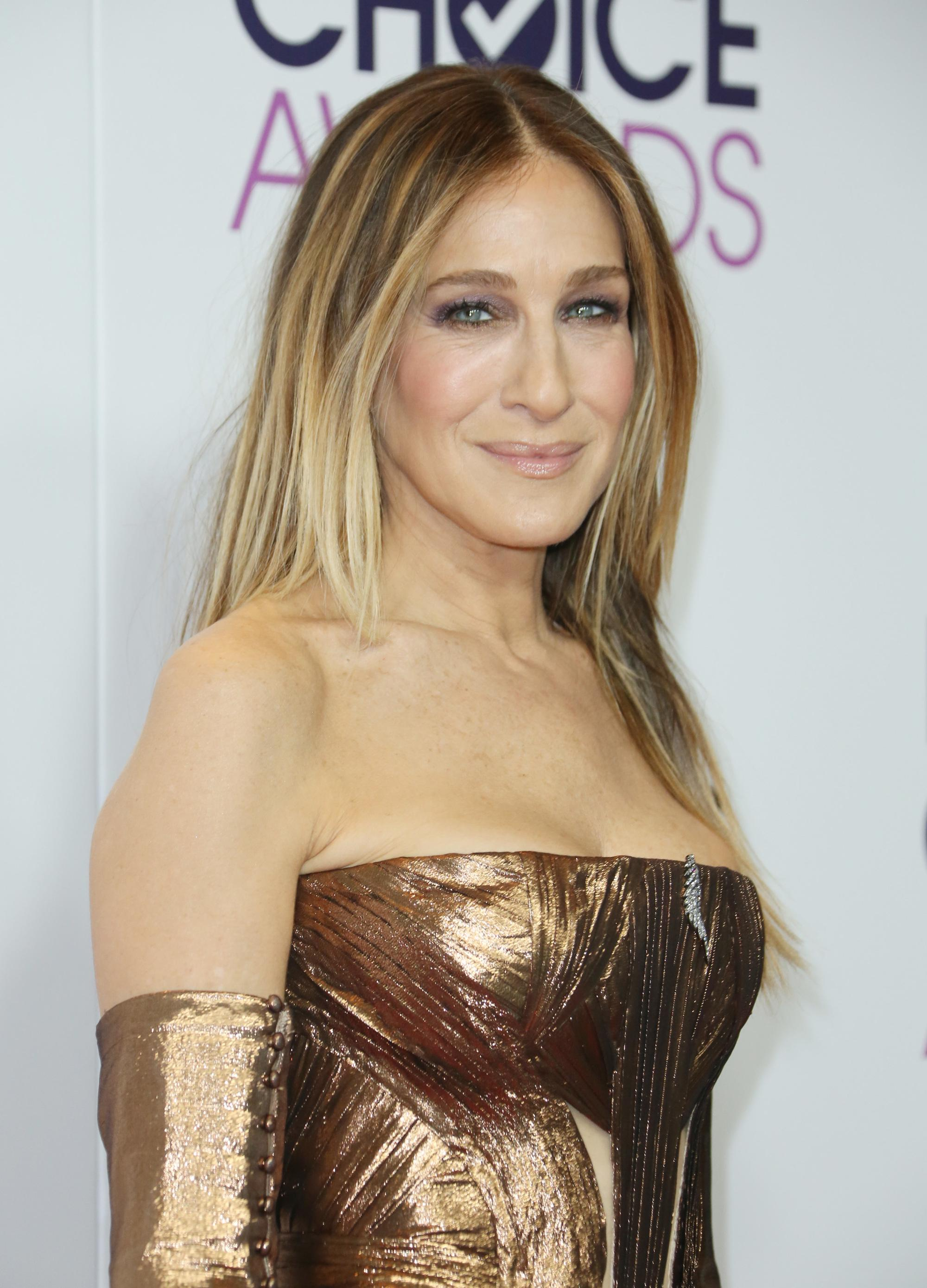 Sarah Jessica Parker with long poker straight blonde hair with highlights at industry red carpet event wearing strapless bronze dress and long gloves