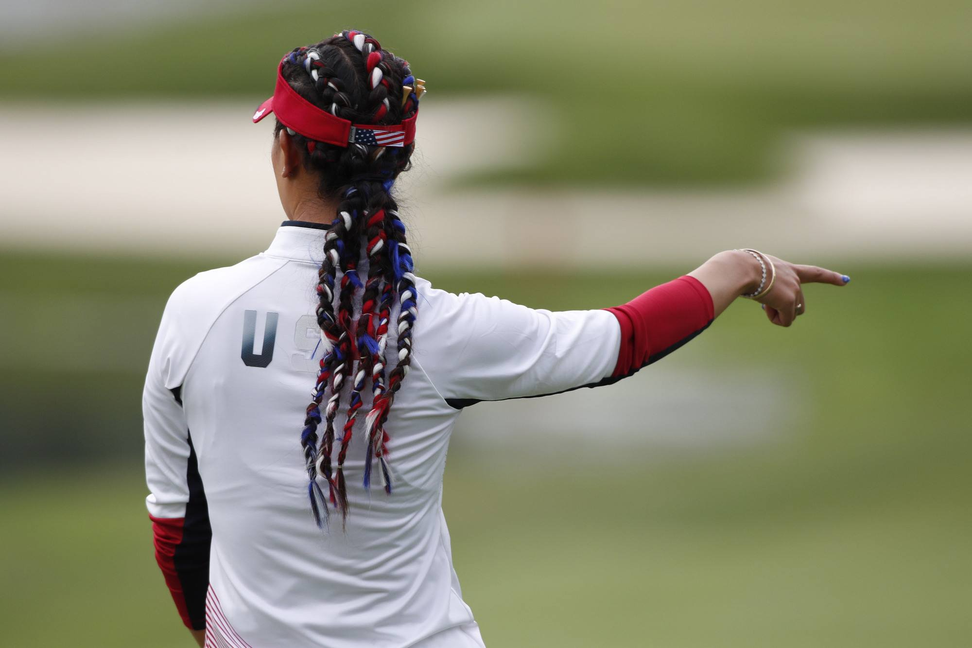 back shot of american golfer michelle wie with ribbon braided hair that's been done to resemble the colours of the US flag