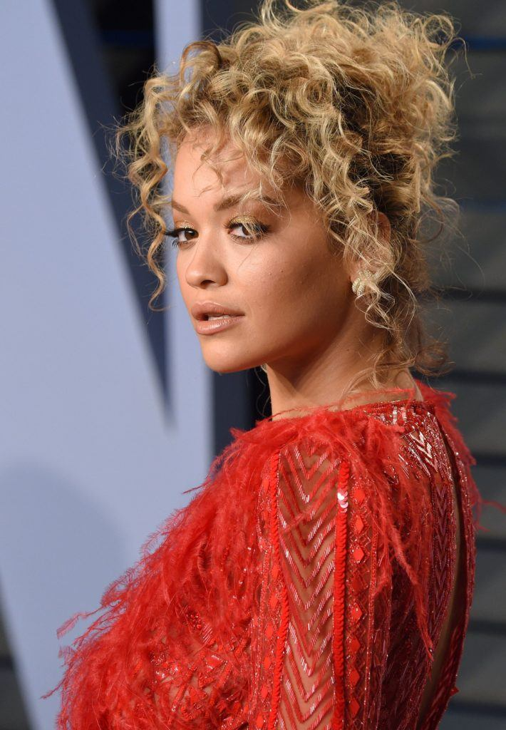 prom hairstyles for medium hair: rita ora on red carpet with dirty blonde curly hair in a undone high updo wearing a red dress