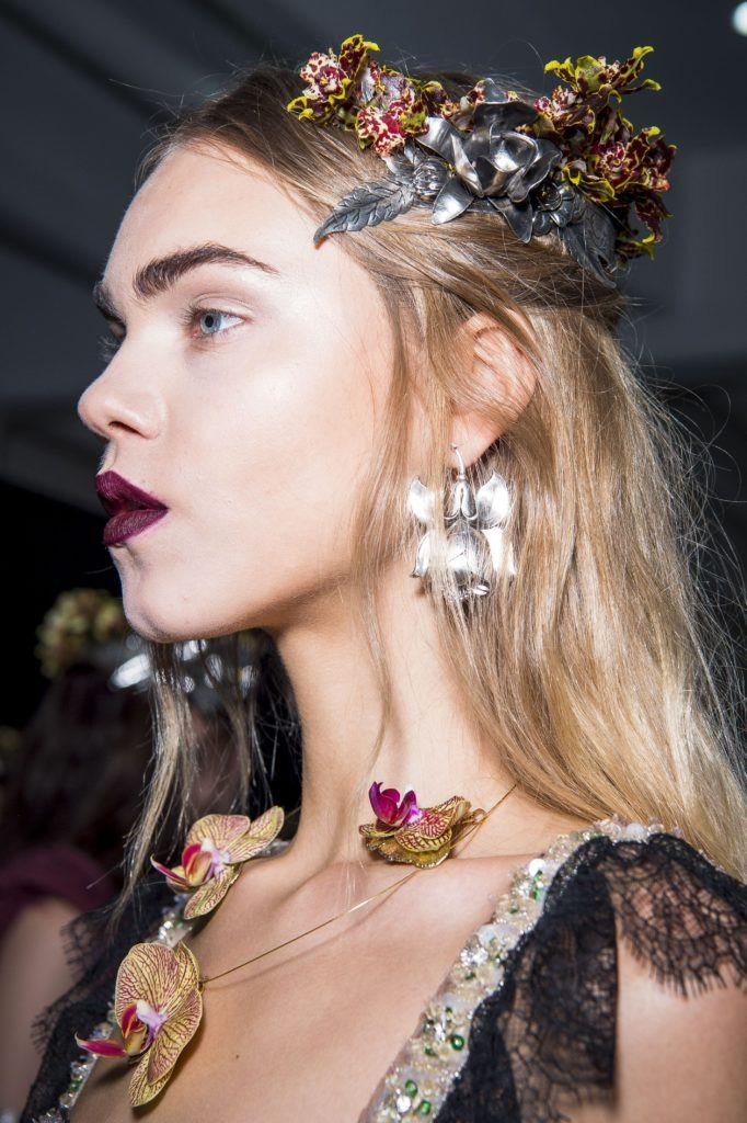 down prom hair looks: close up of model with dirty blonde half up hairstyle with flower clips in it, backstage rodarte and wearing dark lace dress