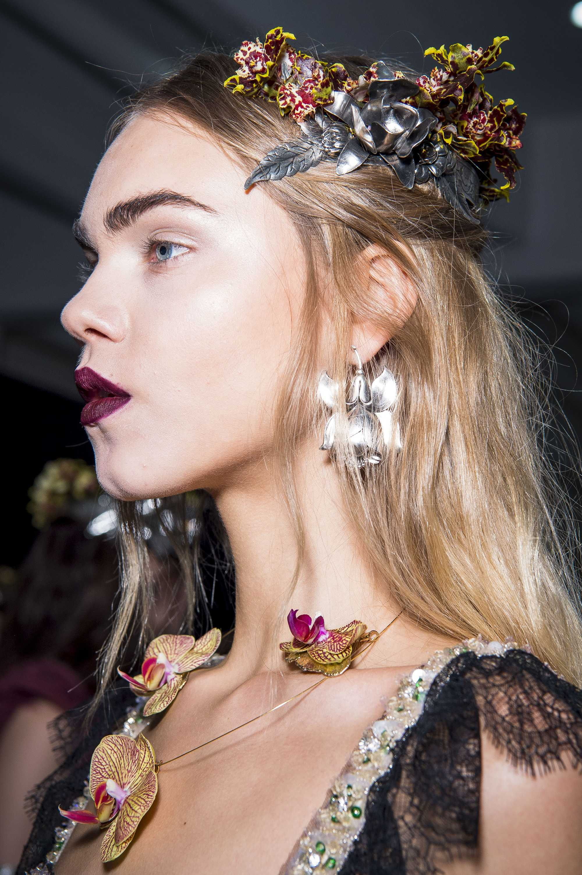 close up of model with half up hairstyle with flower clips in it backstage rodarte