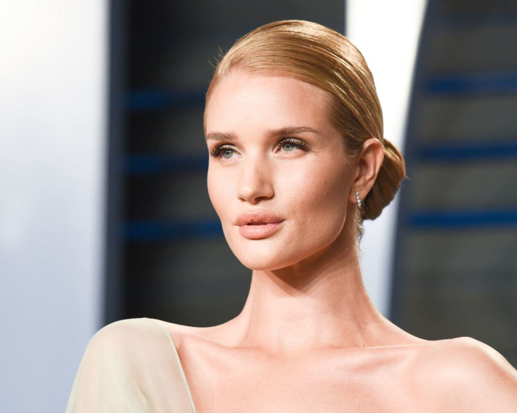 prom updos: model rosie huntington-whiteley on the red carpet with a sleek side bun hairstyle