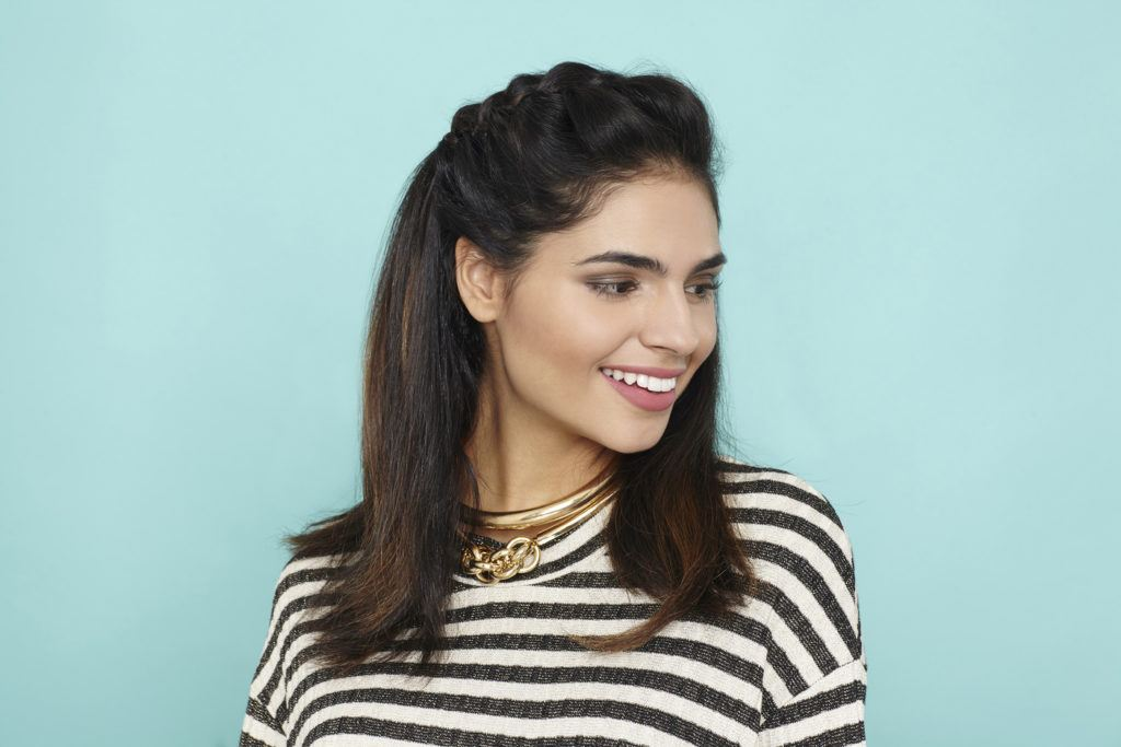 prom hairstyles for medium hair: Brunette model with medium length hair with draped French braid across front of hair wearing striped tshirt
