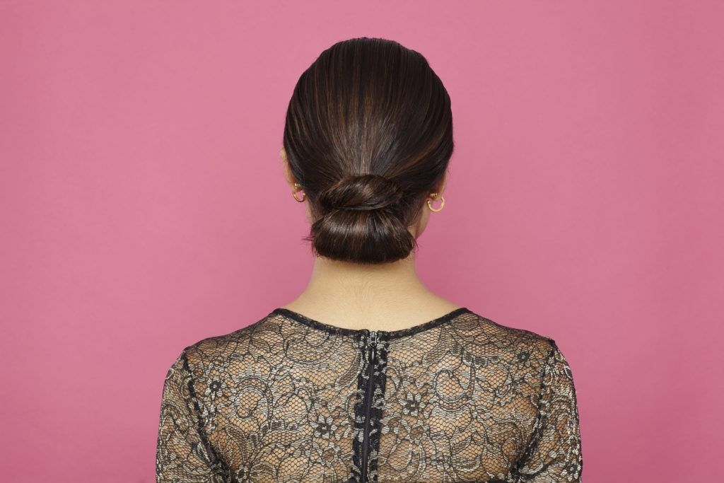 prom hairstyles for medium hair: brown hair model showing of low sleek wrapped tuck bun hairstyle from back view