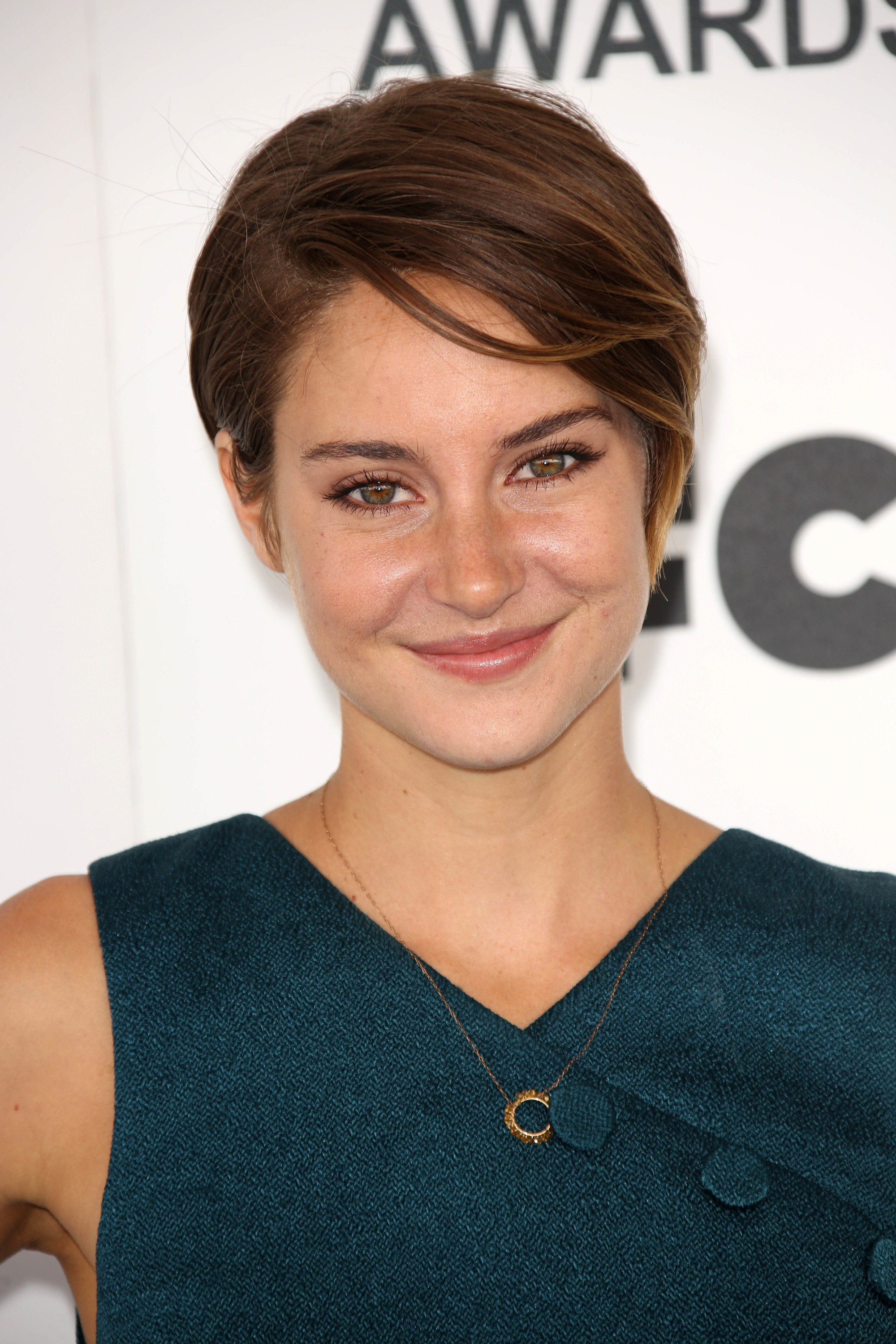 actress shailene woodley wearing a teal dress with brunette pixie cut hair