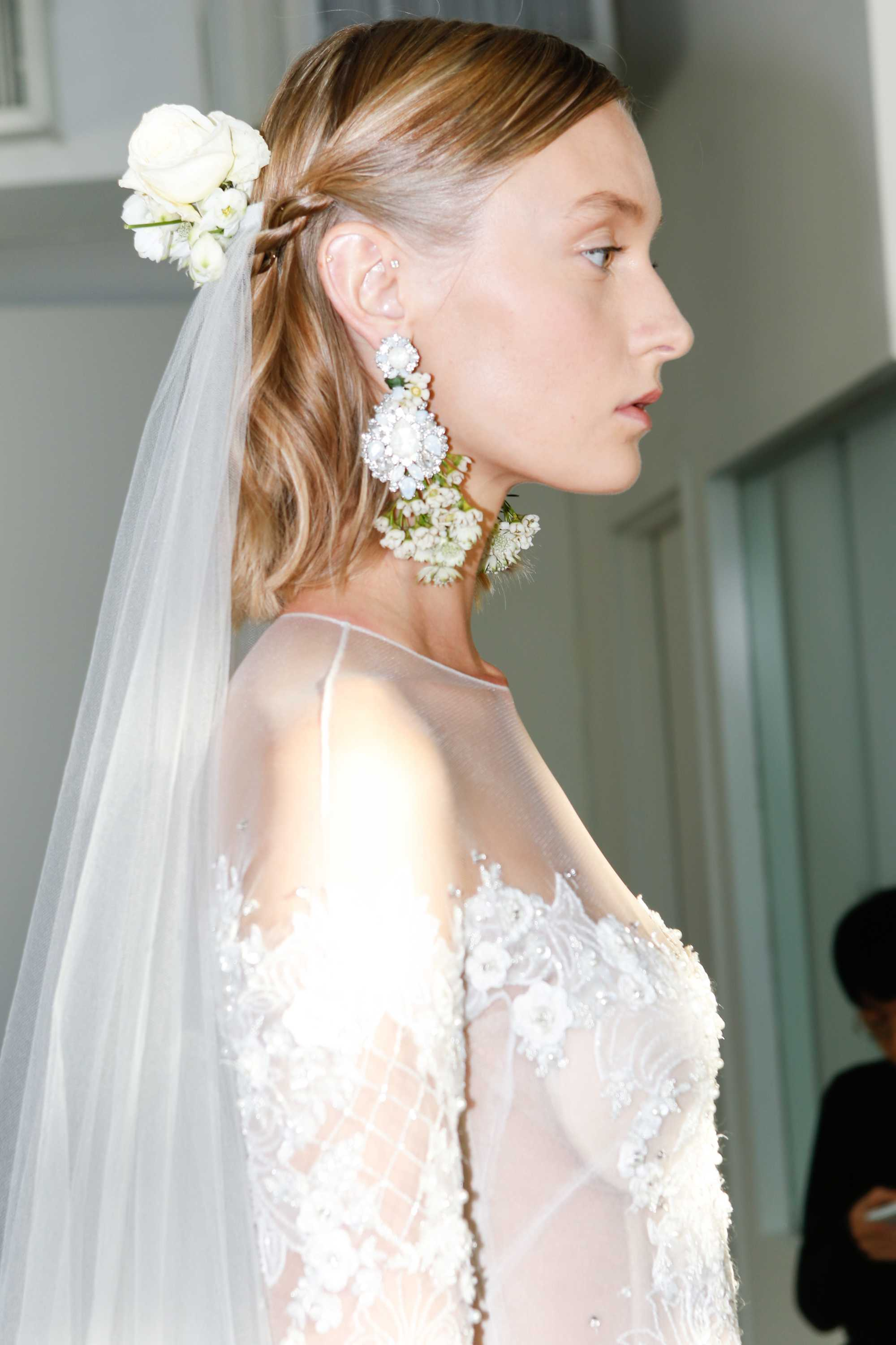 simple wedding hairstyles: side shot of model with half up half hairstyle on the bridal runway at marchesa