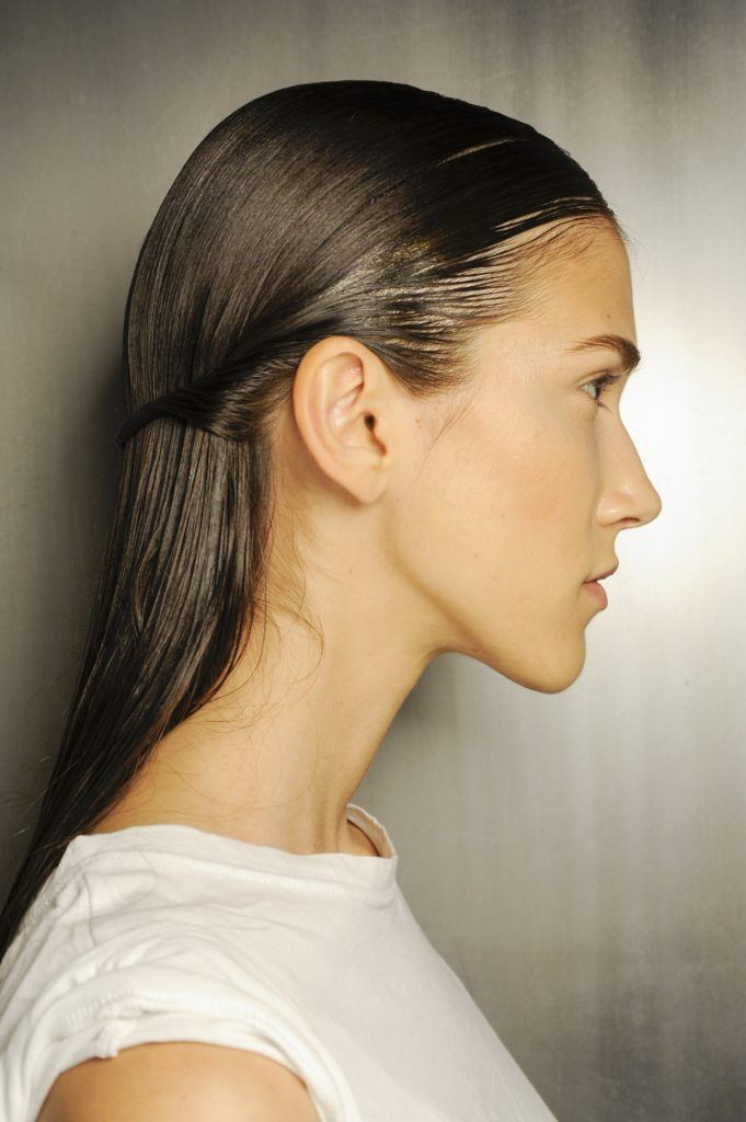 down prom hairstyles: side shot of model with dark brown sleek half up, half down hairstyle, backstage at thakoon
