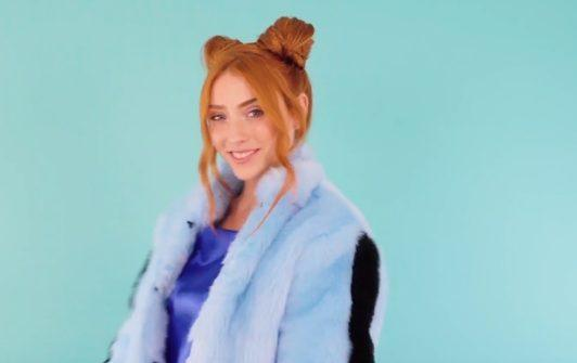 redhead model wearing a blue fur jacket with her hair in space buns