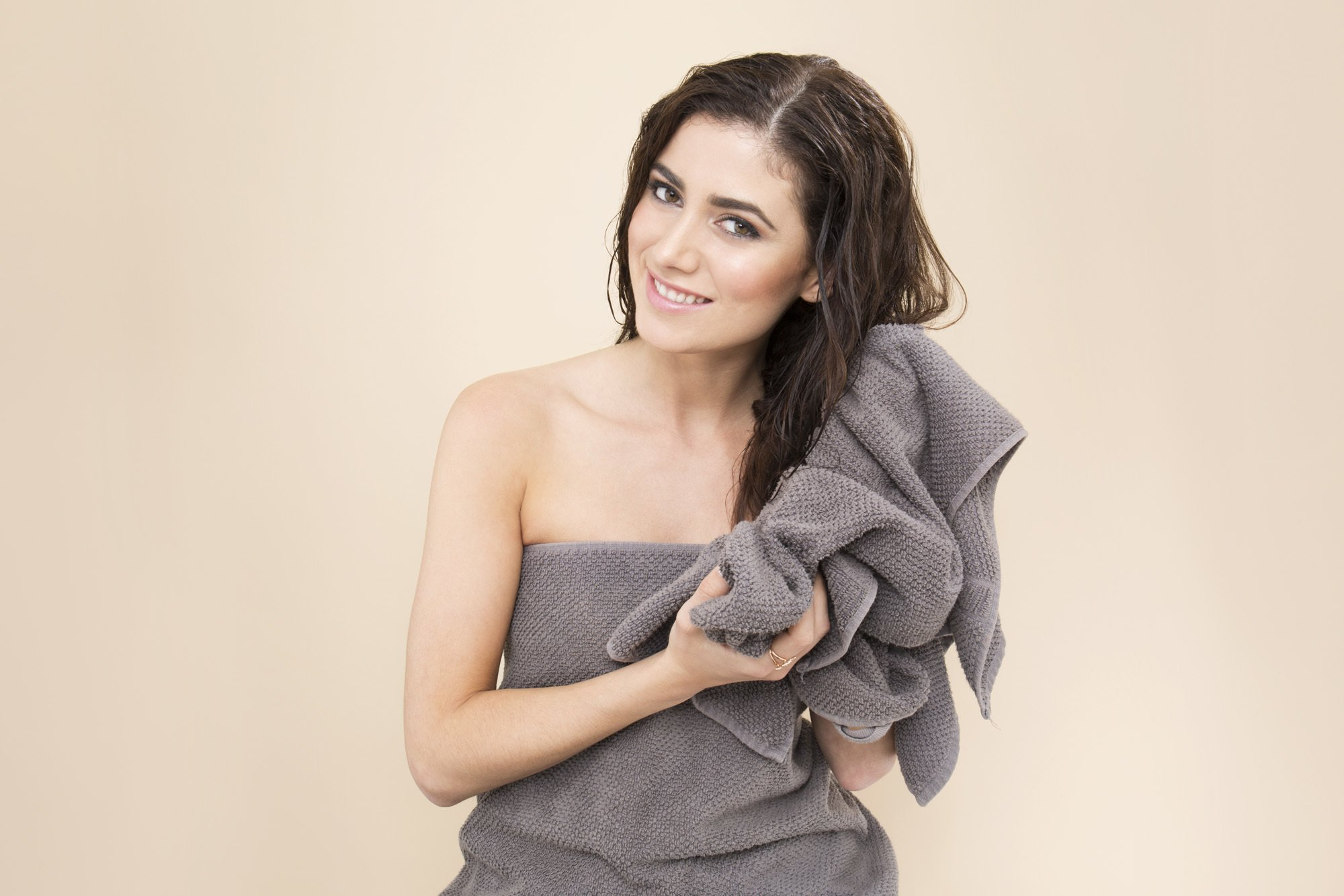 Deep conditioner: Brunette woman in a grey towel drying her damp hair