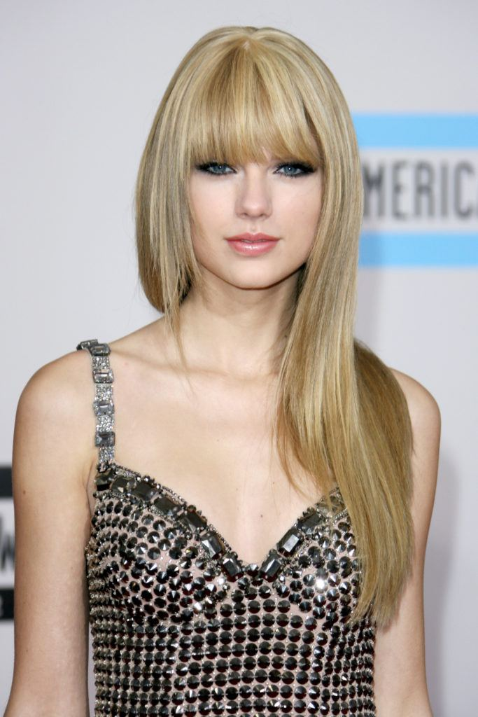singer taylor swift with long straight blonde hair and bangs