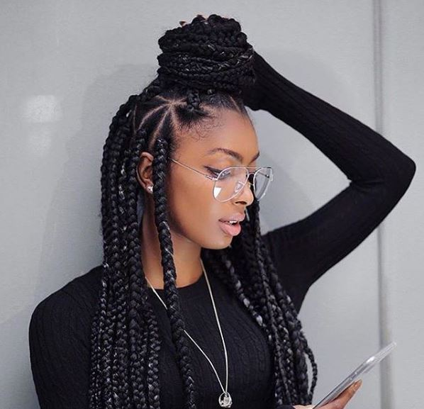 Long big box braid hairstyle with triangle parting worn with clear glasses