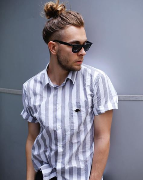 male model with dirty blonde hair with undercut top knot hairstyle