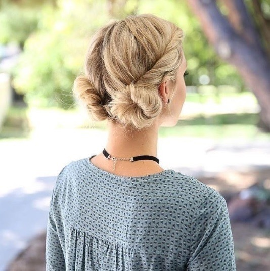 blonde woman wearing a blue patterened top with her hair in twisted low macaron buns