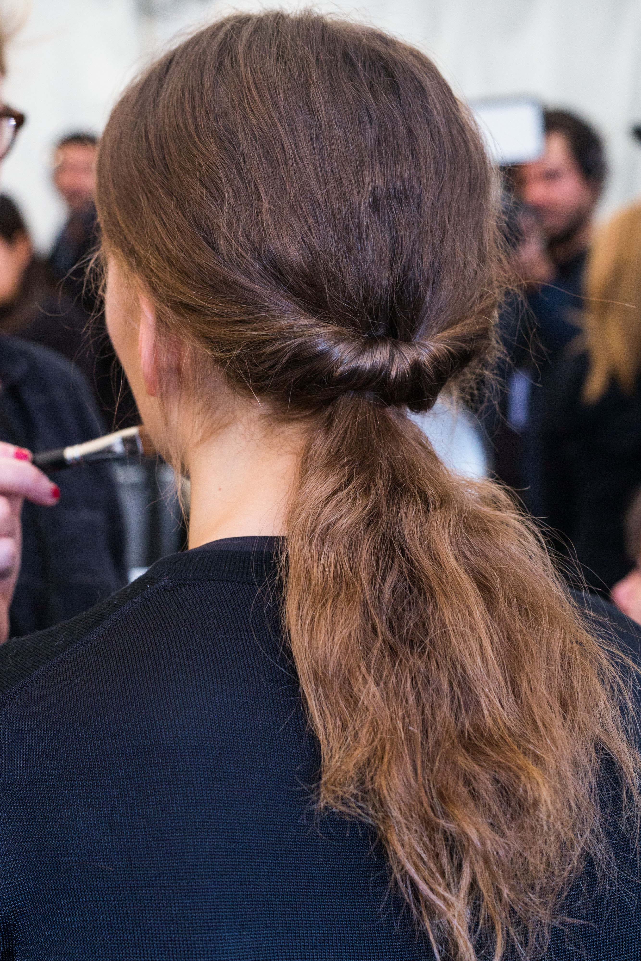 back shot of a brunette model with a twisted frizzy ponytail