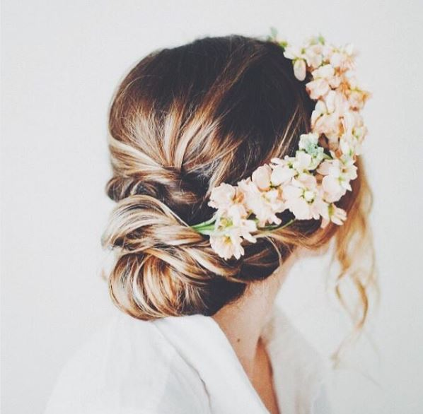 Dark blonde hair in chignon style with pastel coloured flowers for wedding style
