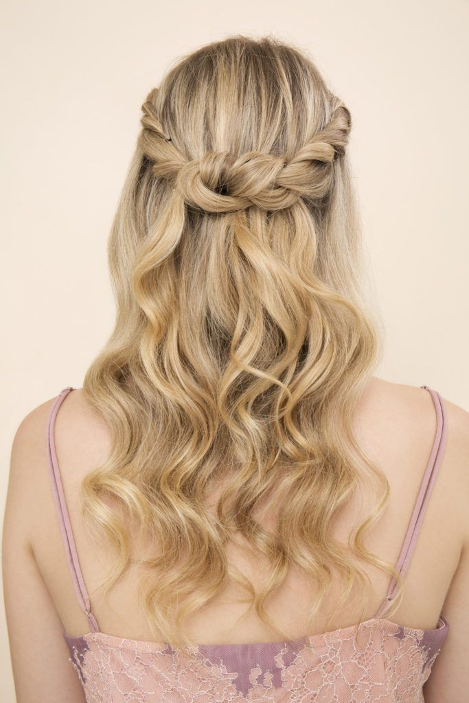 down prom hair ideas: close up shot of a woman with golden blonde hair styled into a half-up, half-down twisted crown, wearing strappy dress and posing in a studio