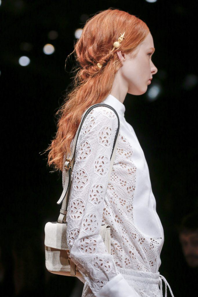 down prom hairstyle ideas: model with ginger hair on the runway with half up half down tuck hairstyle, with metallic band accessory on the valentino runway