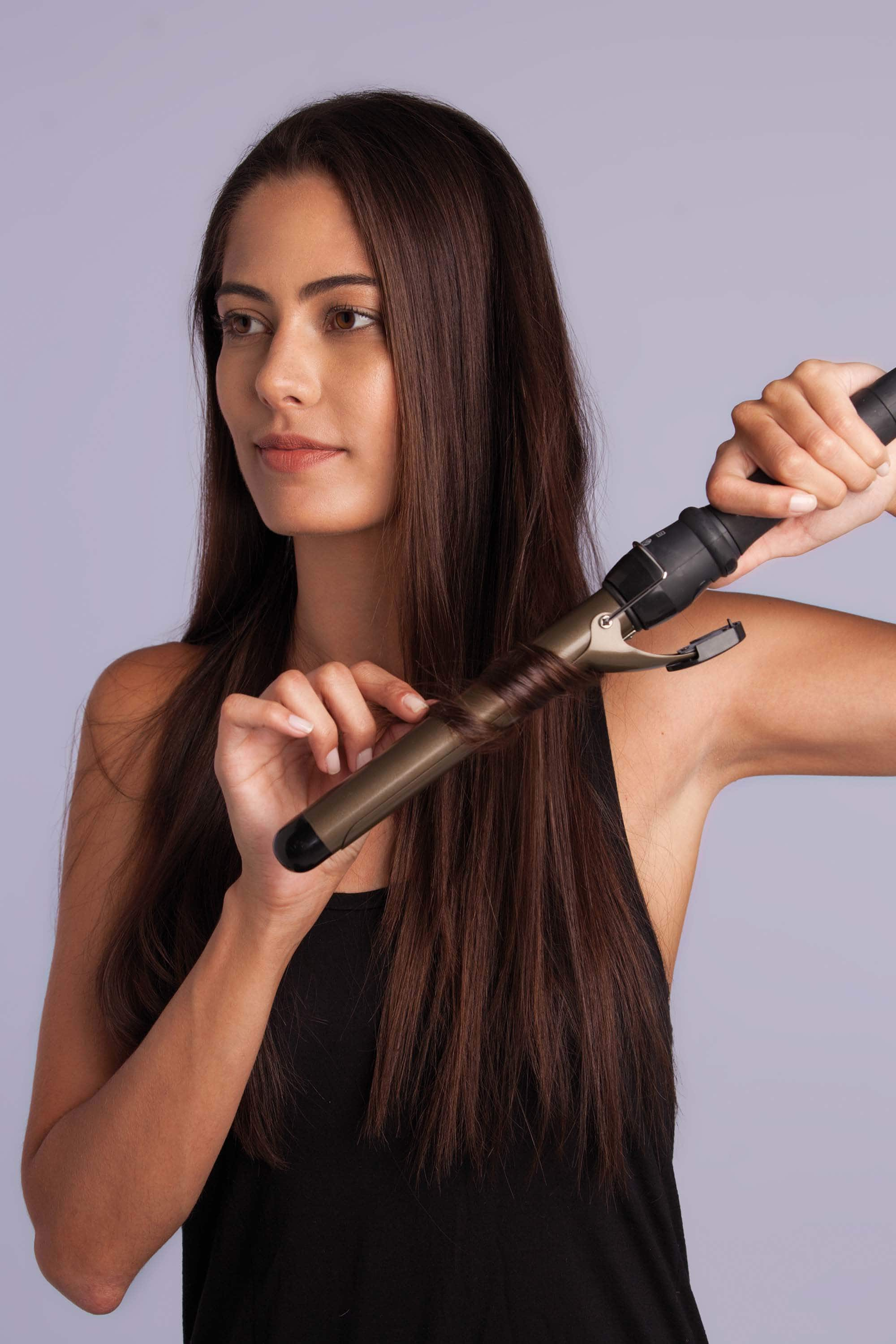 model using curling wand on lon brown hair