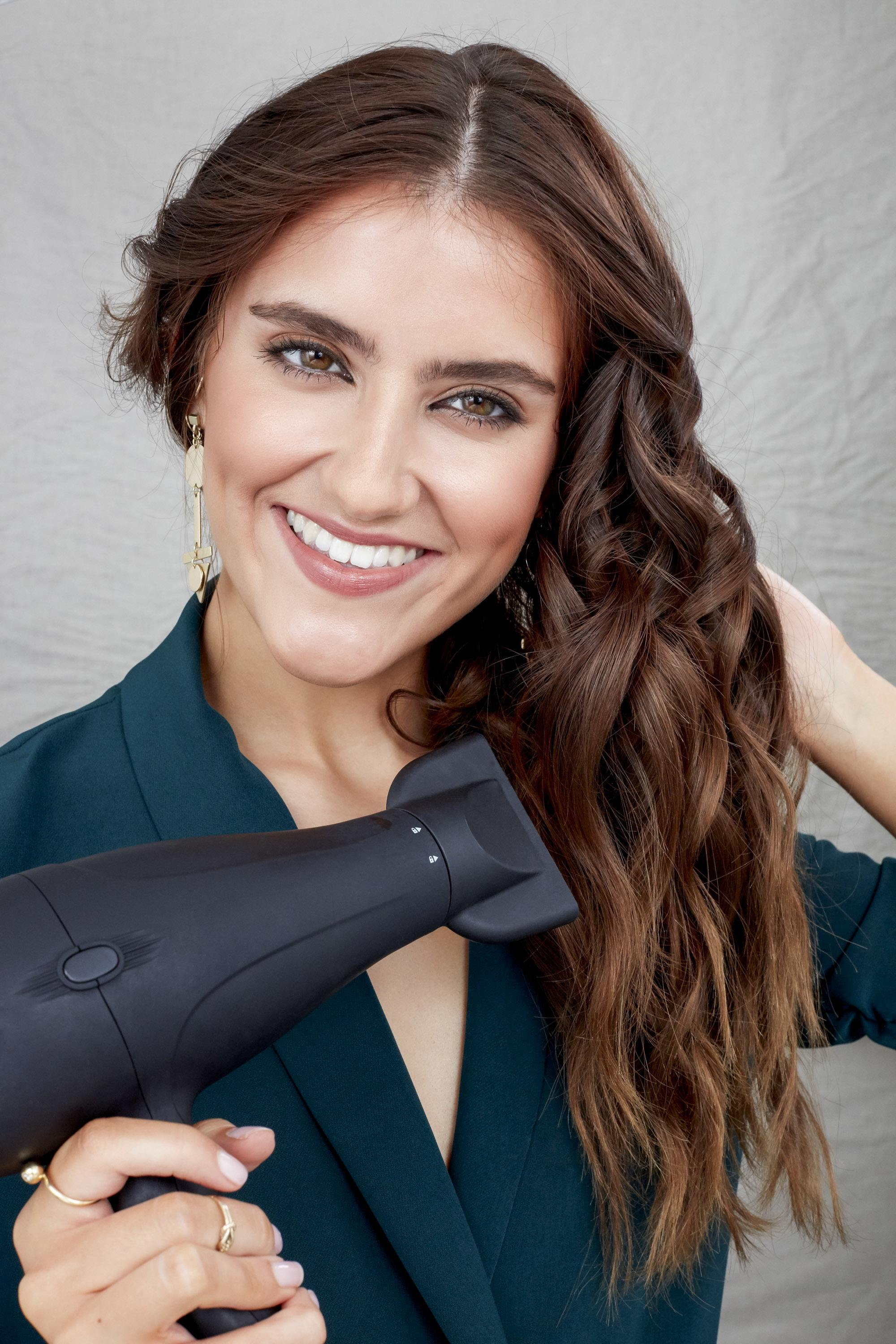 Keratin shampoo: Model with long brown wavy hair holding a hairdryer wearing a dark green jacket.