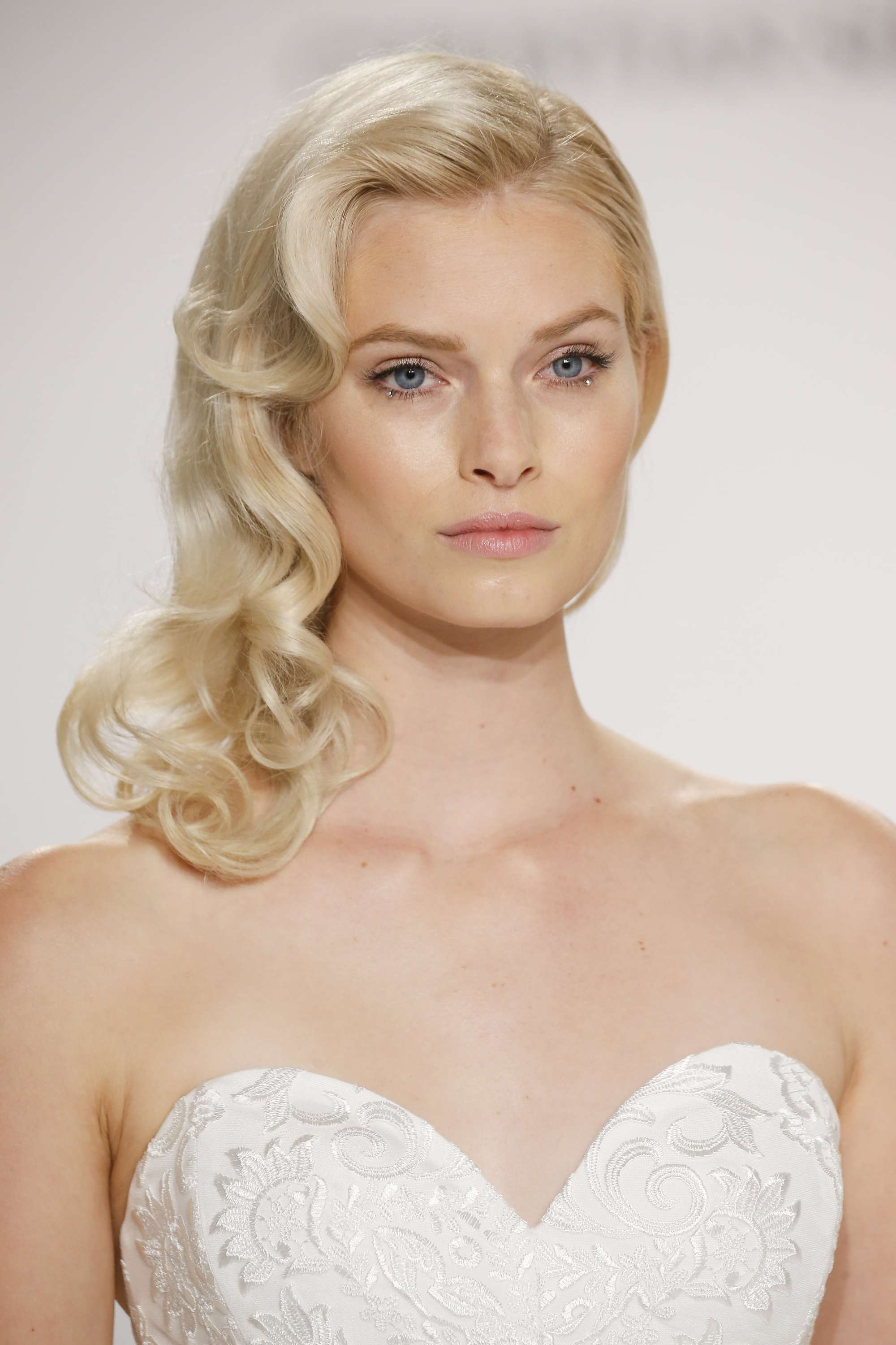 simple wedding hairstyles: shot of model with side swept curls on the runway