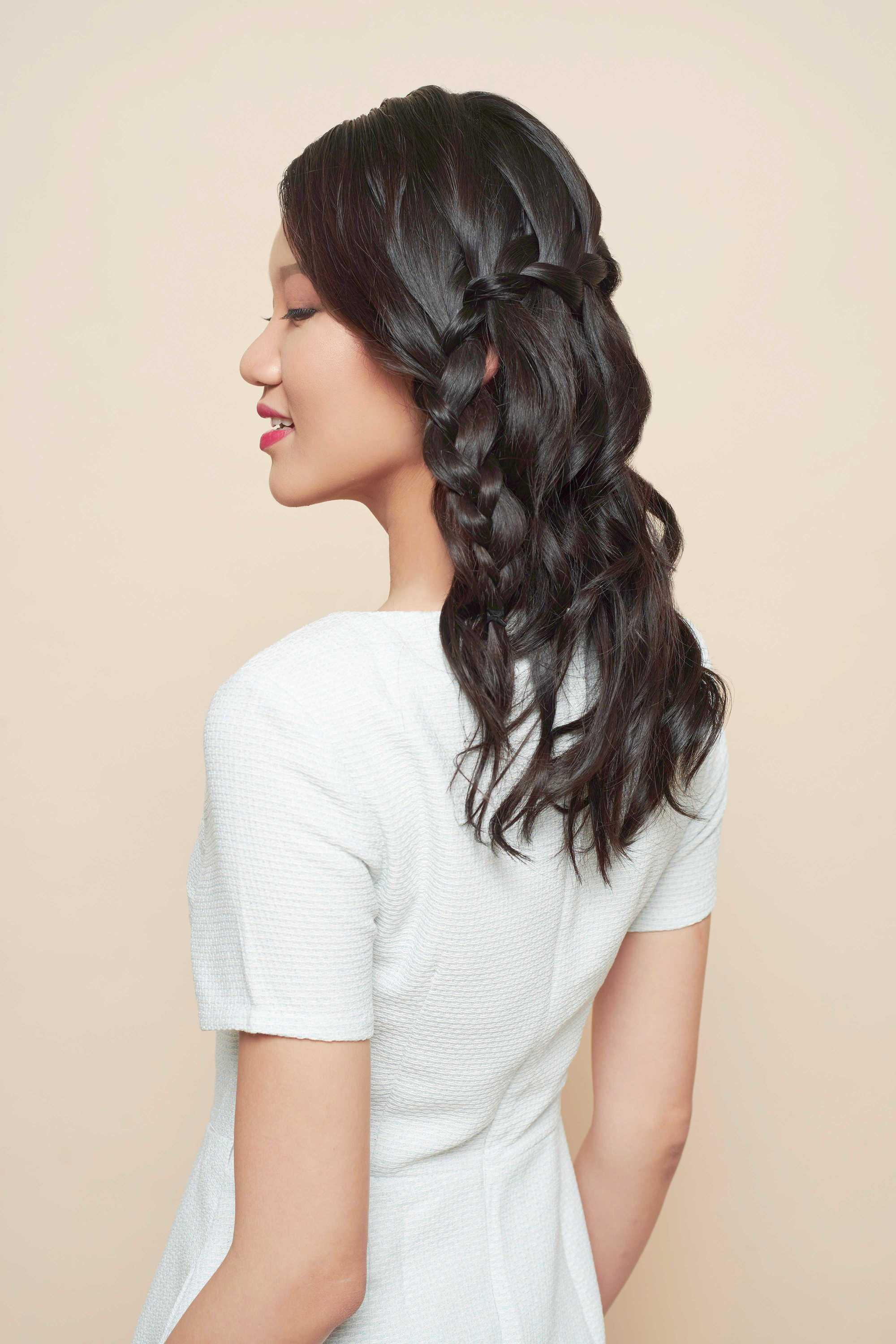 down prom hairstyles: close up shot of a model with dark brown hair styled into a waterfall braid, wearing white dress and posing in a studio