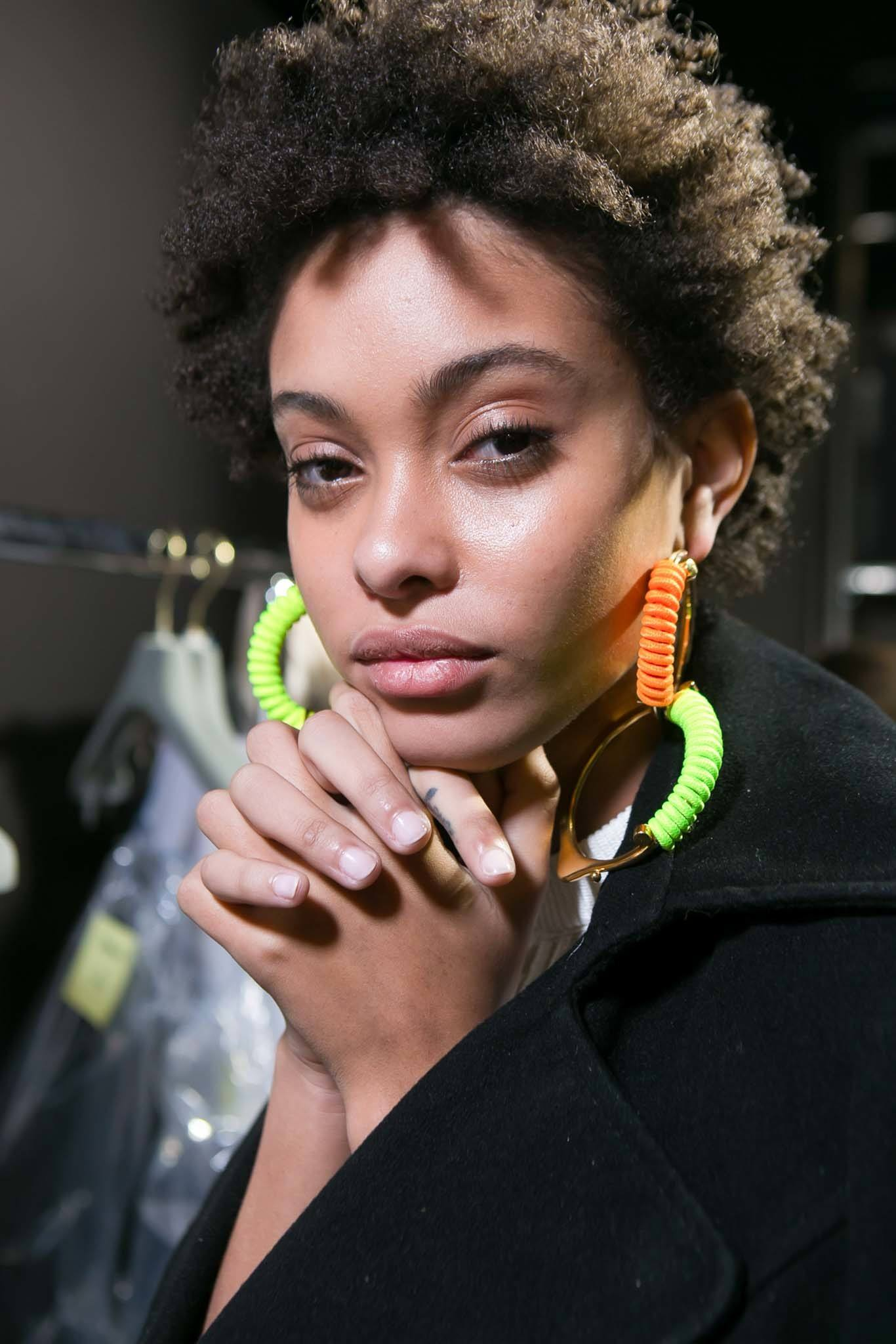 best leave in conditioner for dry hair: backstage shot of model with short afro hair backstage posing