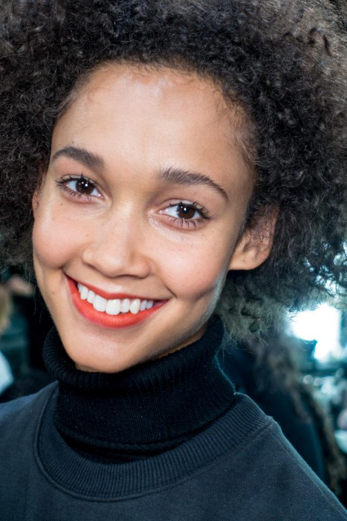 afro haired model backstage at a fashion show wearing red lipstick
