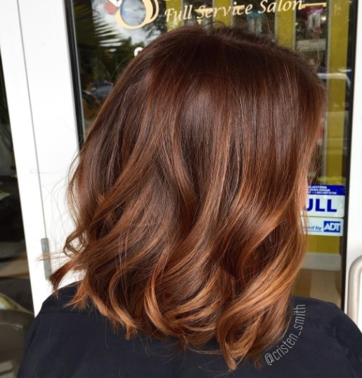 back view of a woman with sunkissed auburn highlighted hair