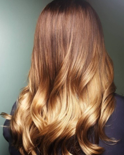 back view of a woman with auburn to blonde ombre hair