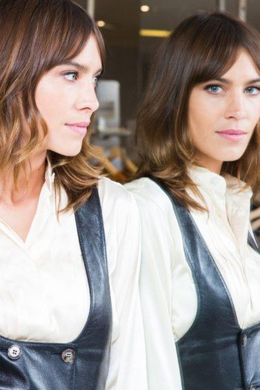 the best bangs directory: close up shot of alexa chung with bardot bangs hairstyle staring into the mirror