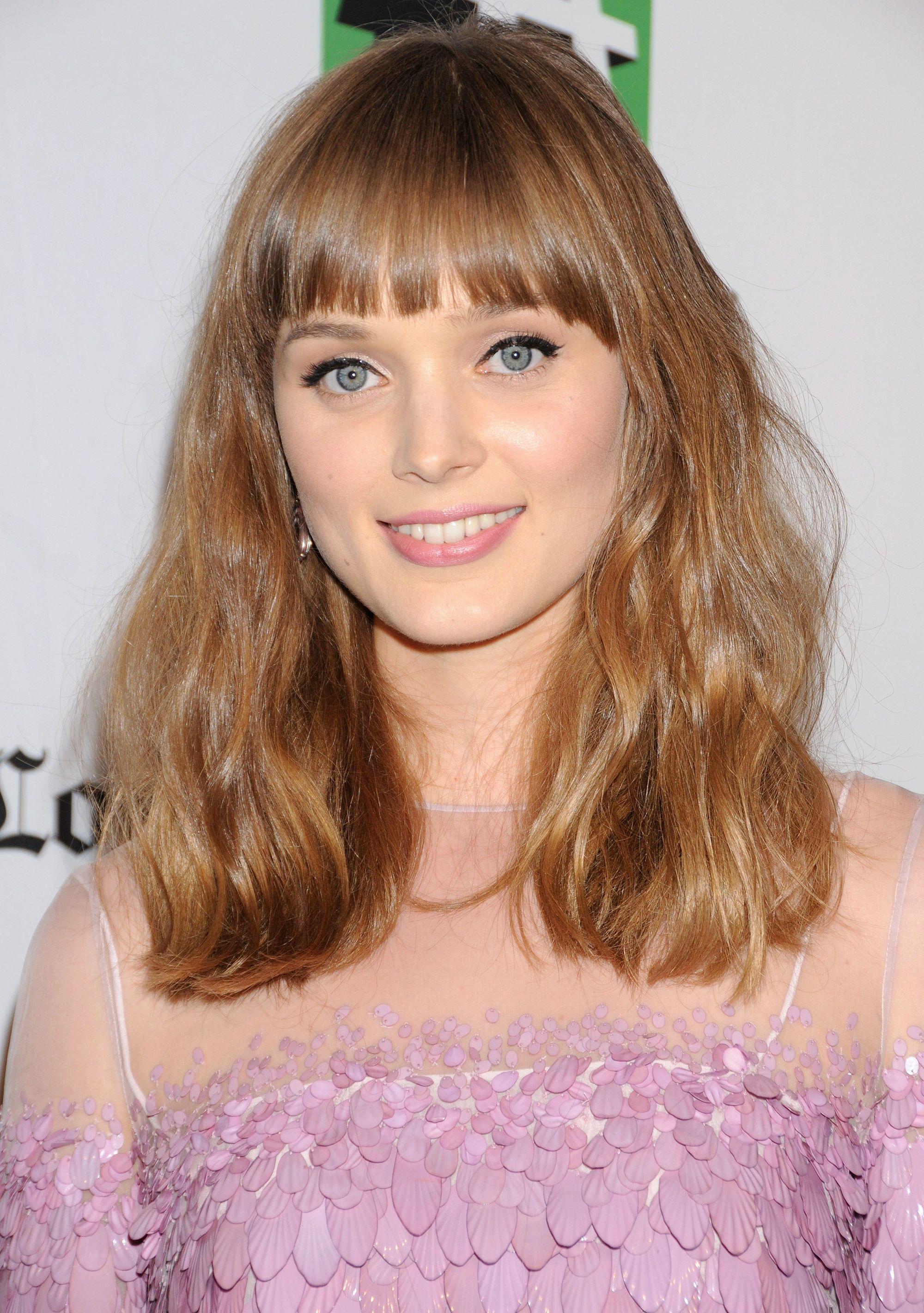 bangs for fine hair: bella heathcote with long bangs and wavy hair smiling