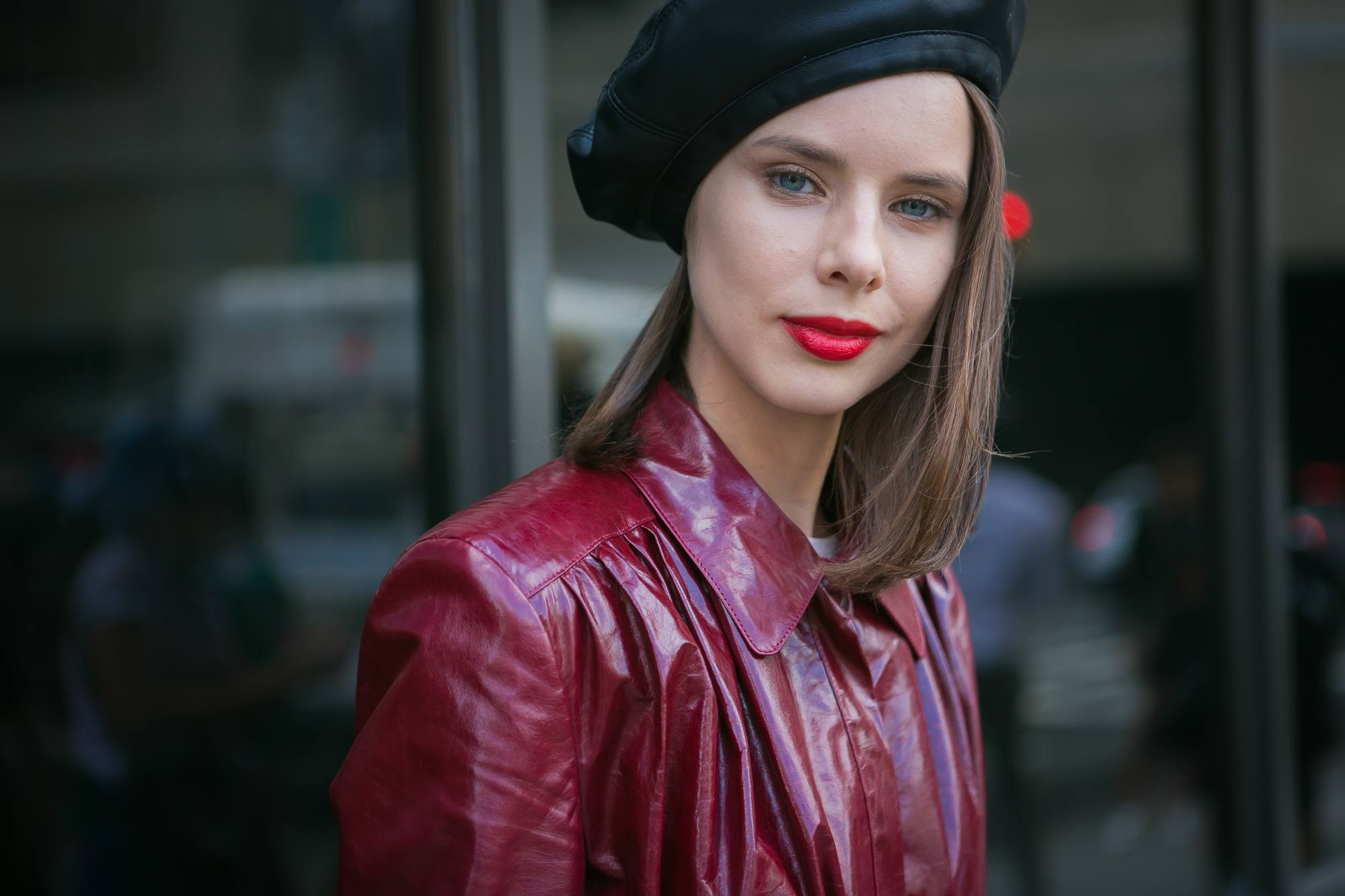 close up shot of woman with beret hairstyle, wearing red leather