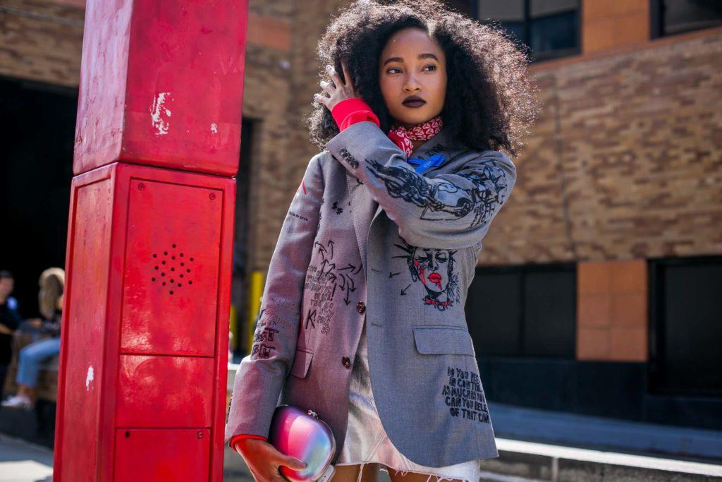 new york fashion ss18: shot of street style model with big curly hairstyle with blazer