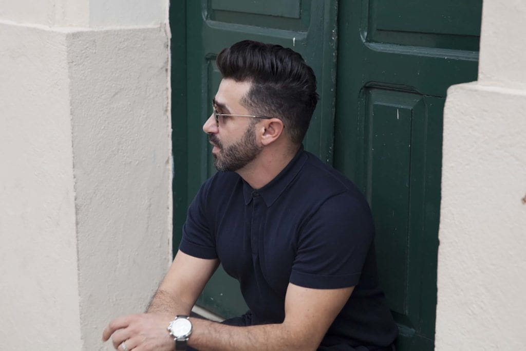 close up shot of man with taper fade haircut with quiff