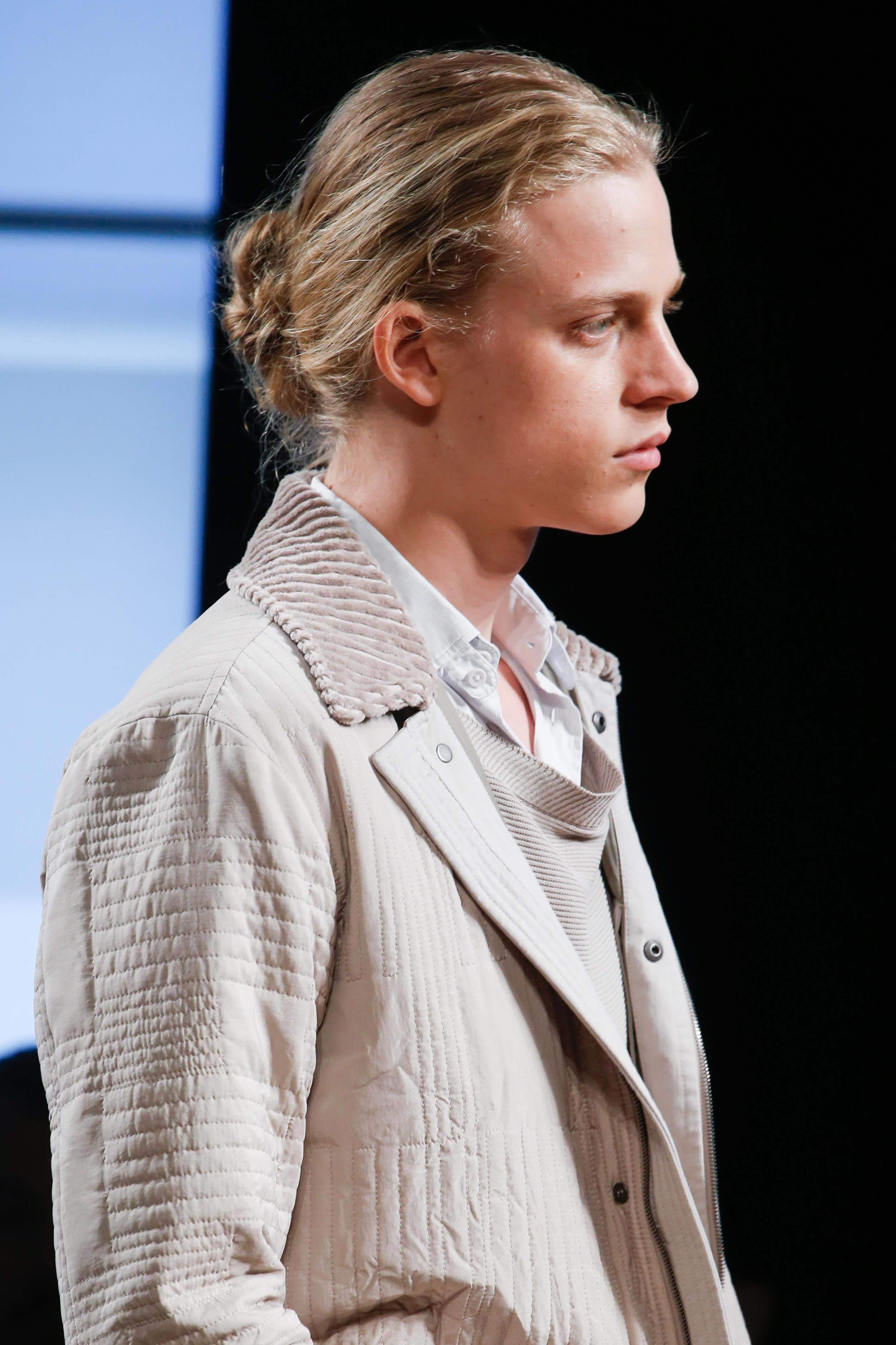 blonde male model on runway with messy low bun