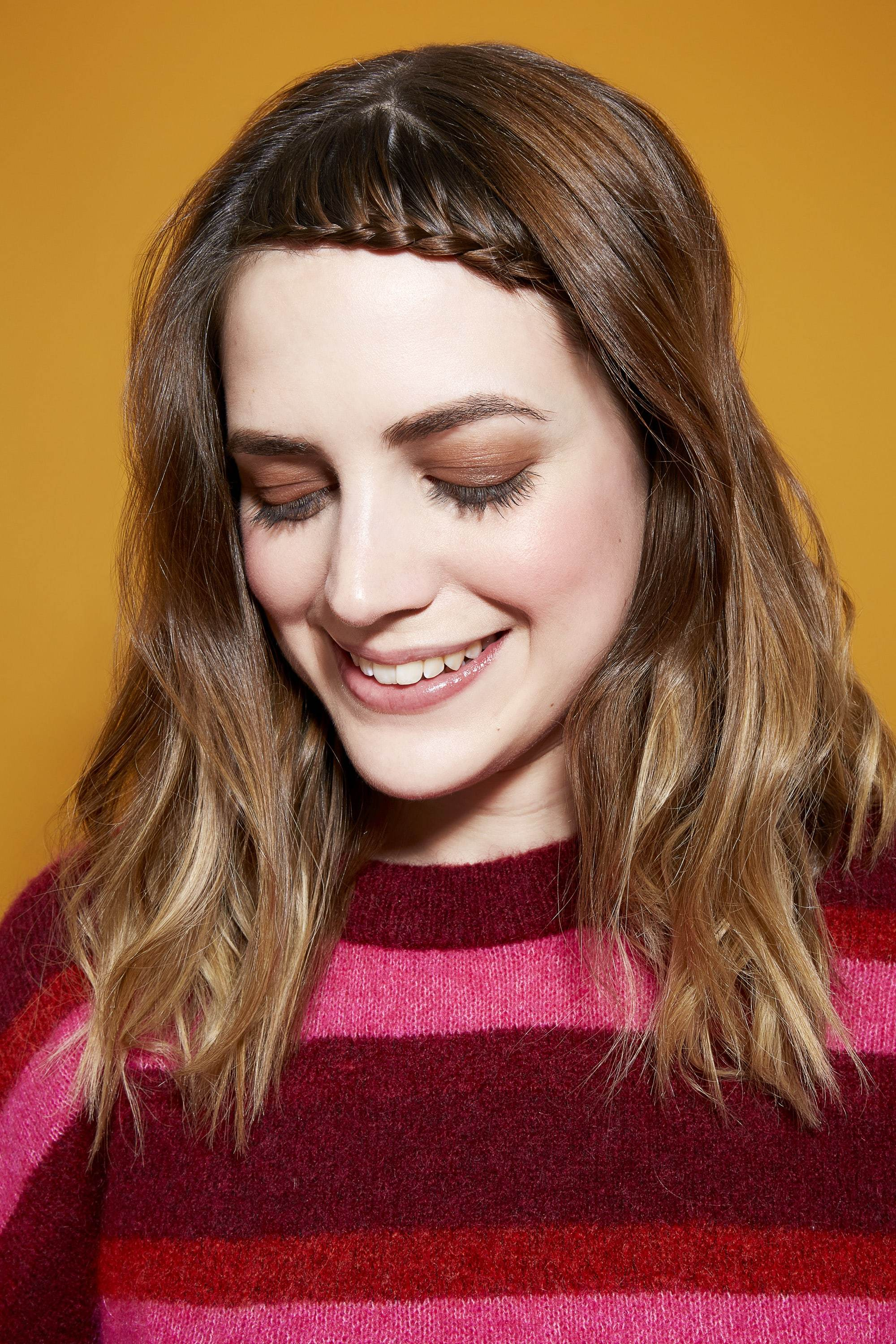 Easy braids for long hair: Brunette woman with braided bangs, wearing a pink and burgundy striped jumper