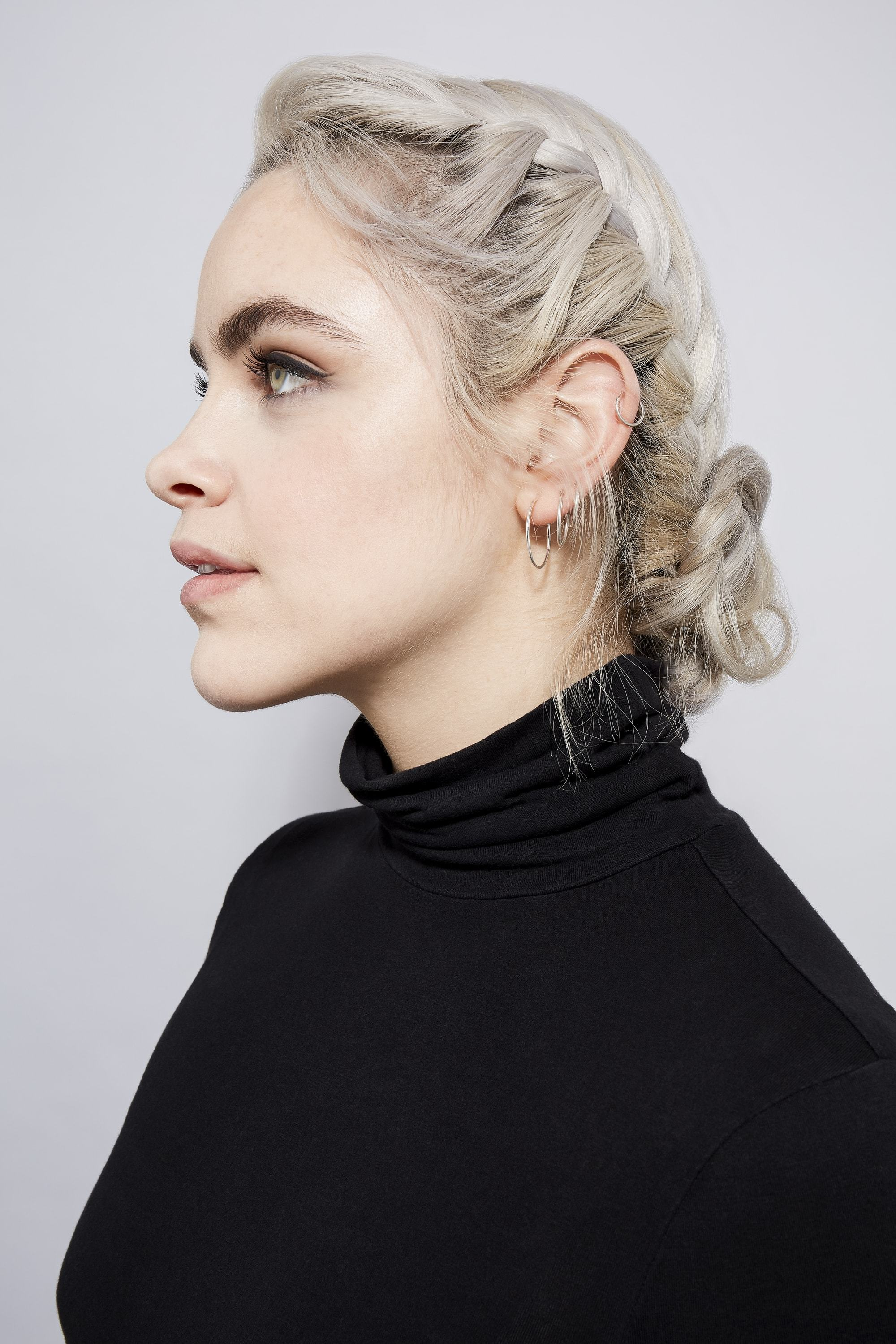 Easy braids for long hair: Side profile of a woman with ash blonde hair in a braided bun, wearing a black roll neck top