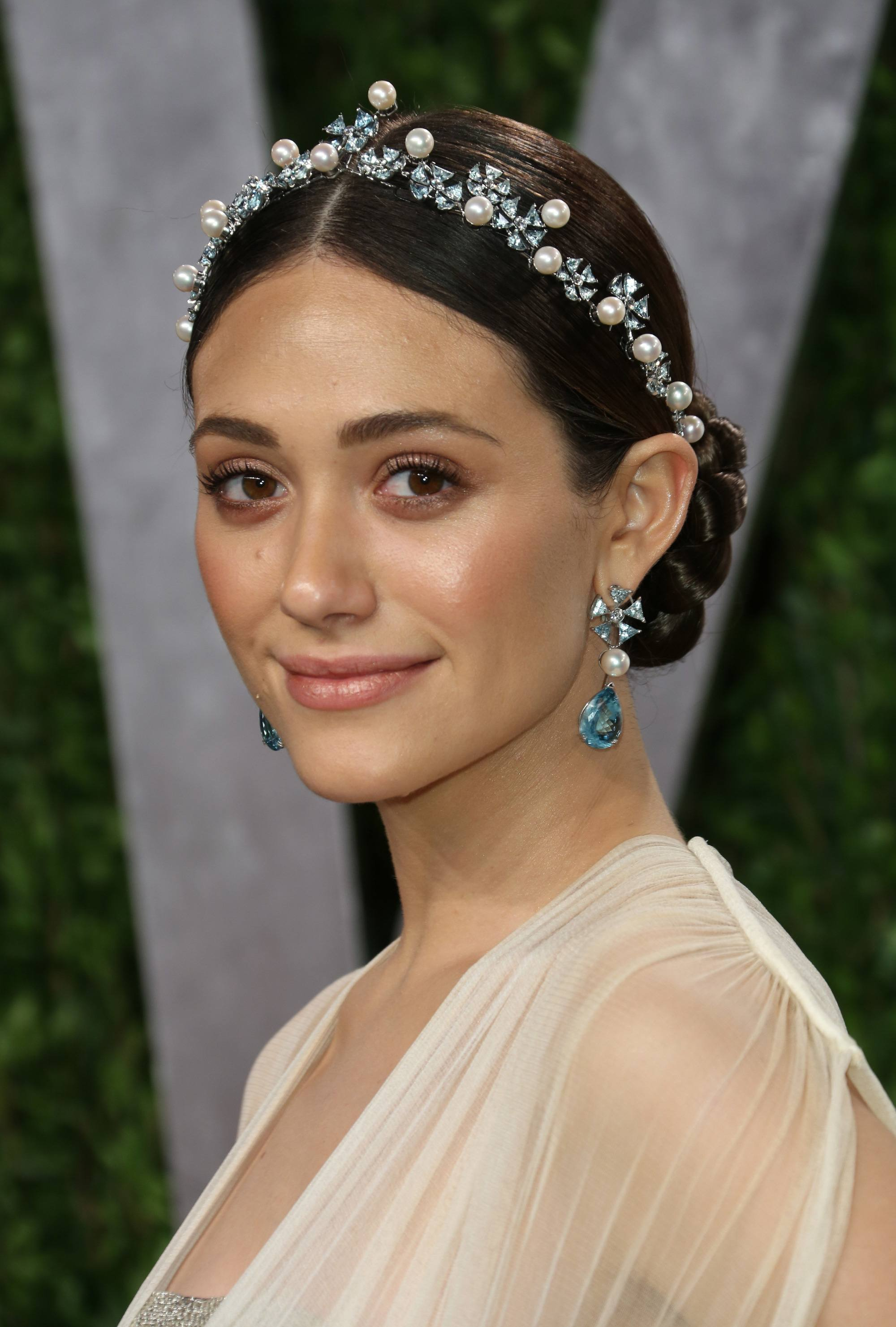 close up shot of emmy rossum with braided low bun and pearls in her hair on the red carpet