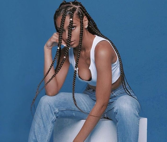 Dookie braids: Close up shot of a woman with contrast parting and long dookie braids.